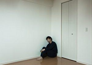部屋の隅で座る男性の写真