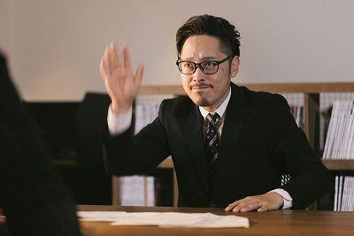 手を挙げる男性